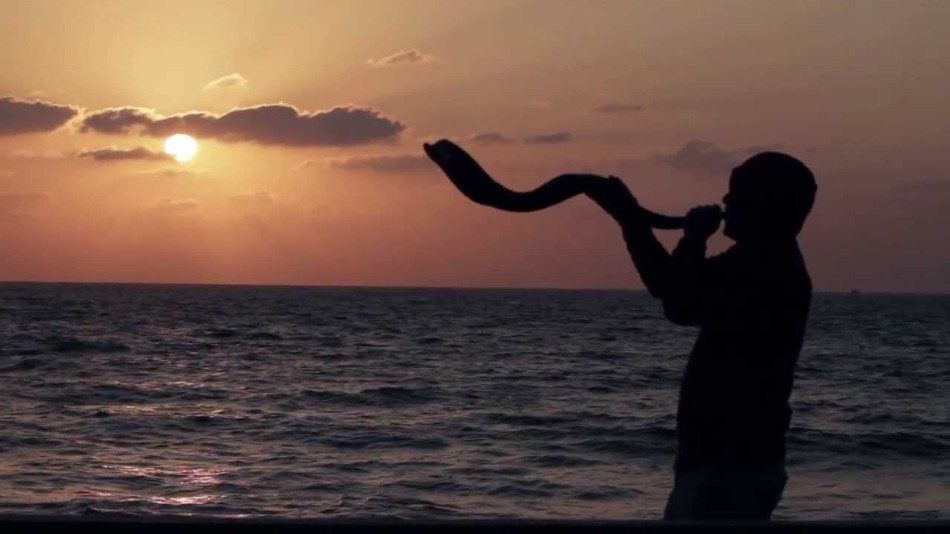 Image of person blowing shofar at ocean