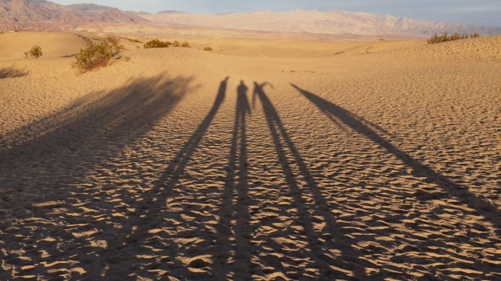 Photo of four people's long shadows in Death Valley by Shai Gluskin